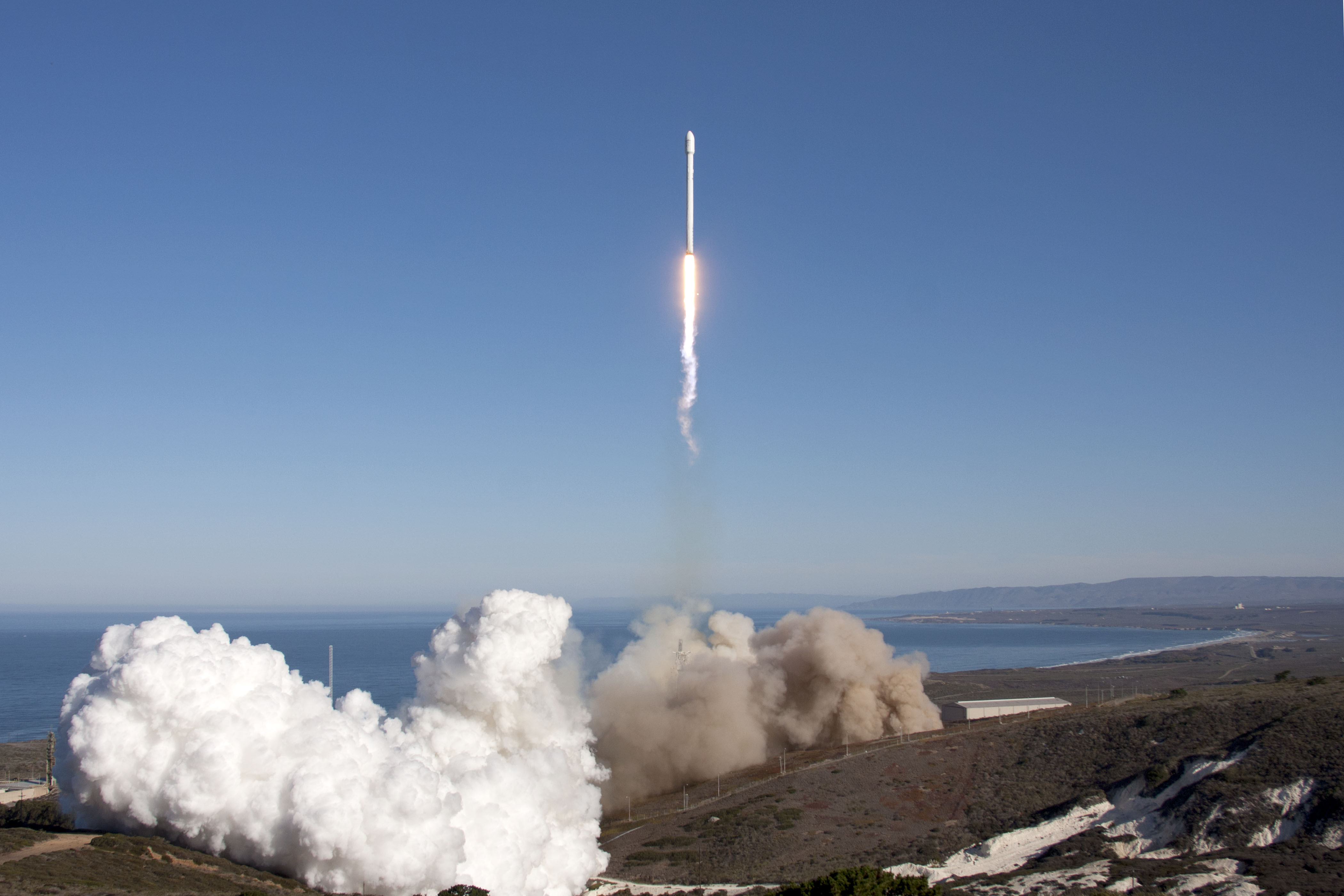 An upgraded SpaceX Falcon 9 rocket roars to life in this split-screen ...